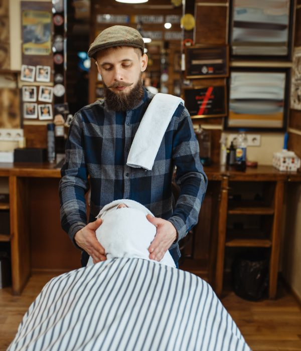 Barber and customer with towel on face, barbershop
