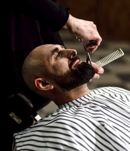Men's fashion. The barber scissors beard of brutal man in the stylish barbershop